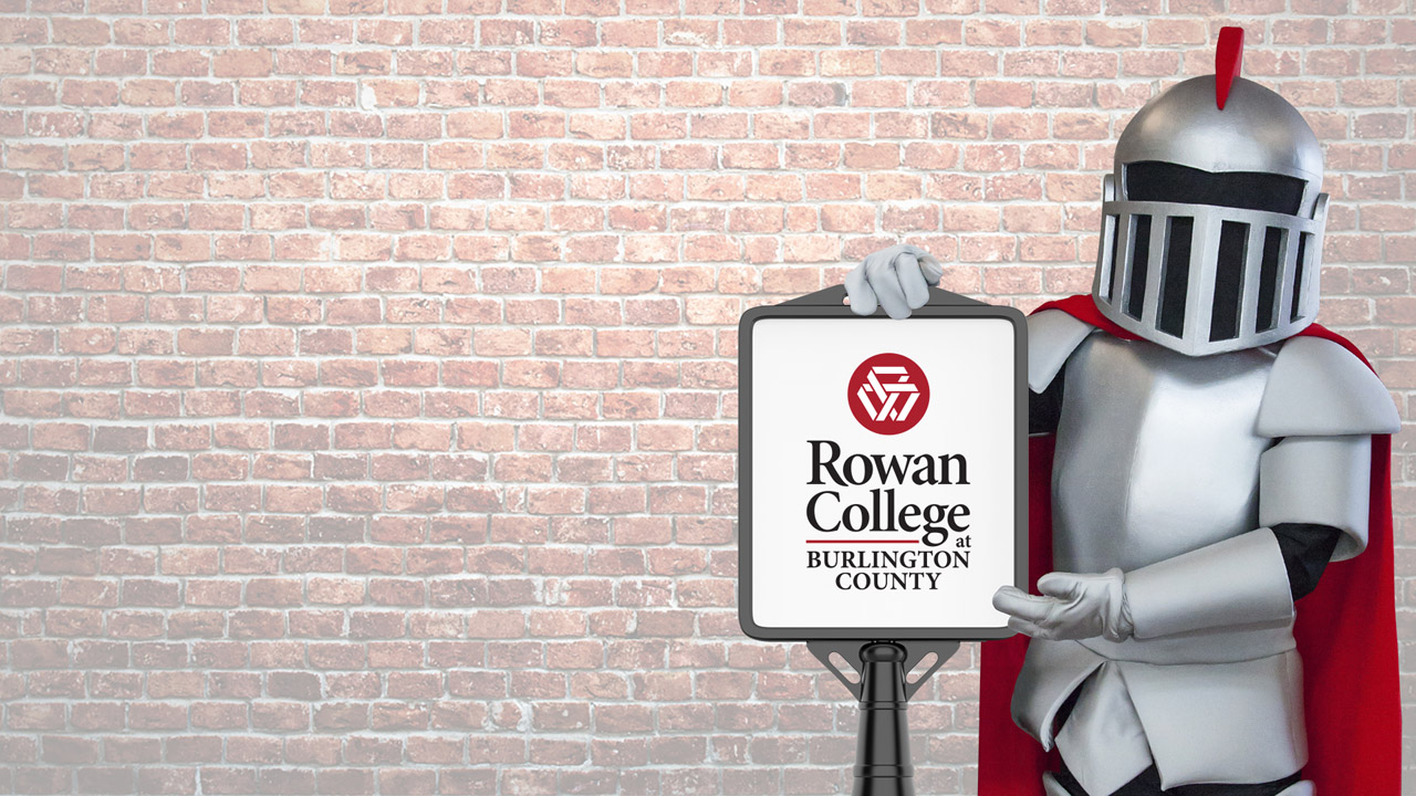 Barry holding a sign with the college logo on it in front of a brick background