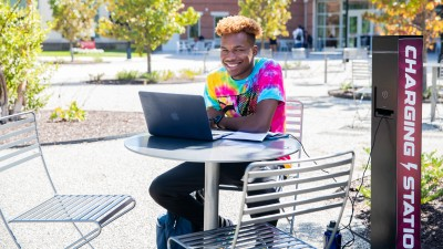 male student sitting at table in quad on laptop