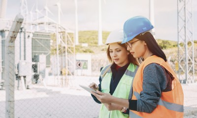 women standing at construction site reviewing info on clipboard