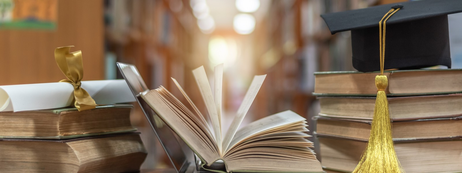 Books in a library with a diploma and graduation cap