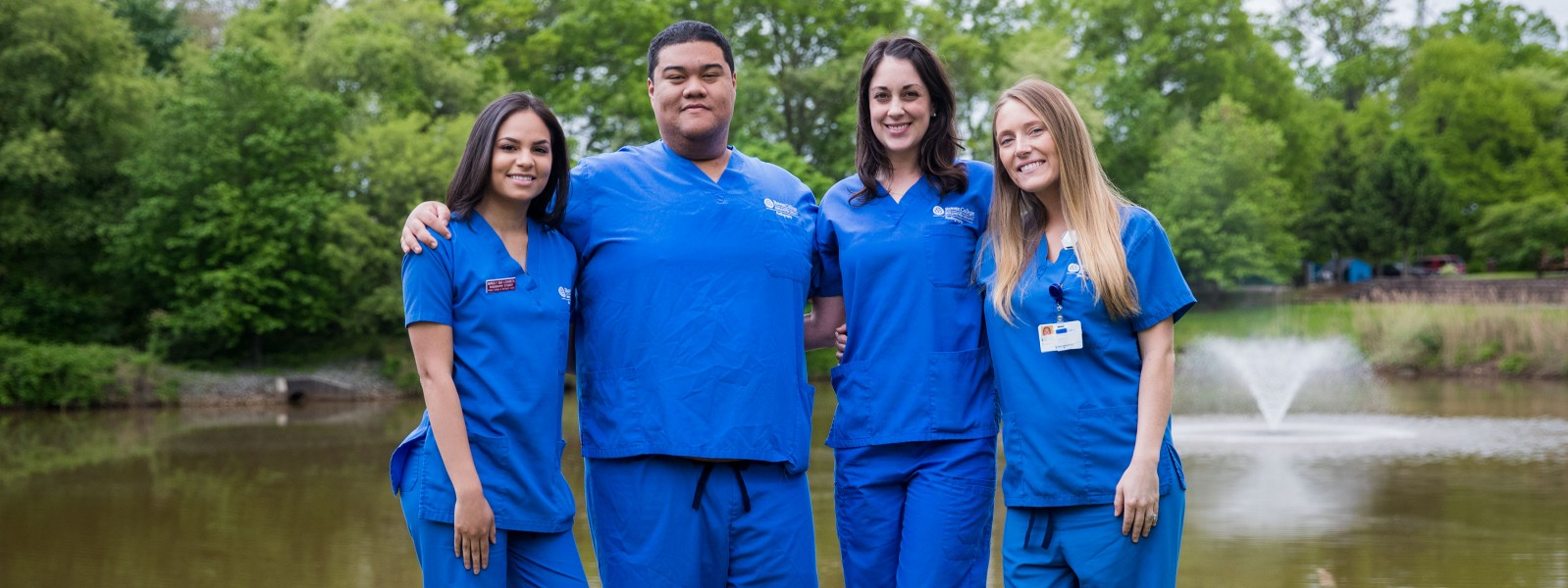 Radiography students outside of the health sciences center wearing blue RCBC scrubs.