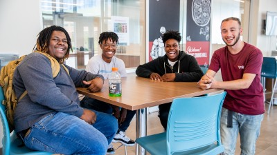 4 students sitting around table smiling