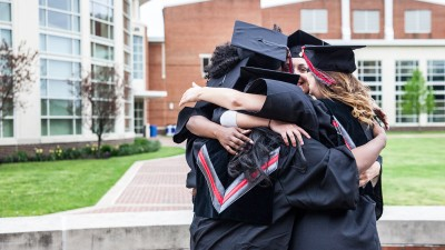 Graduates hugging in the quad